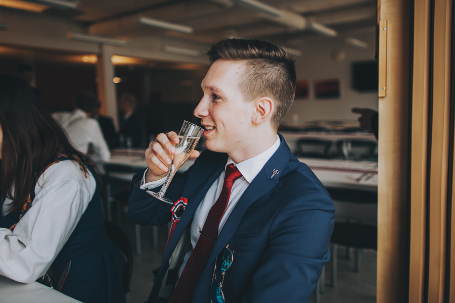 Boy drinking and wearing a red tie