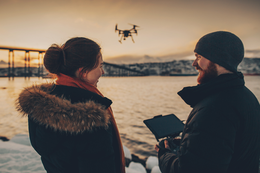 Girl and boy flying a drone