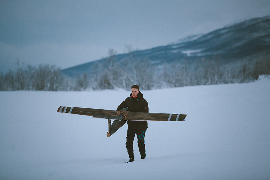 Boy fetching the fixed-wing drone