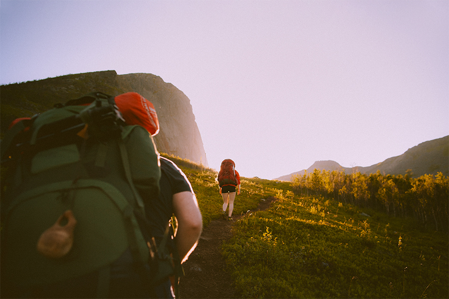 Two hikers with backpacks walking upwards