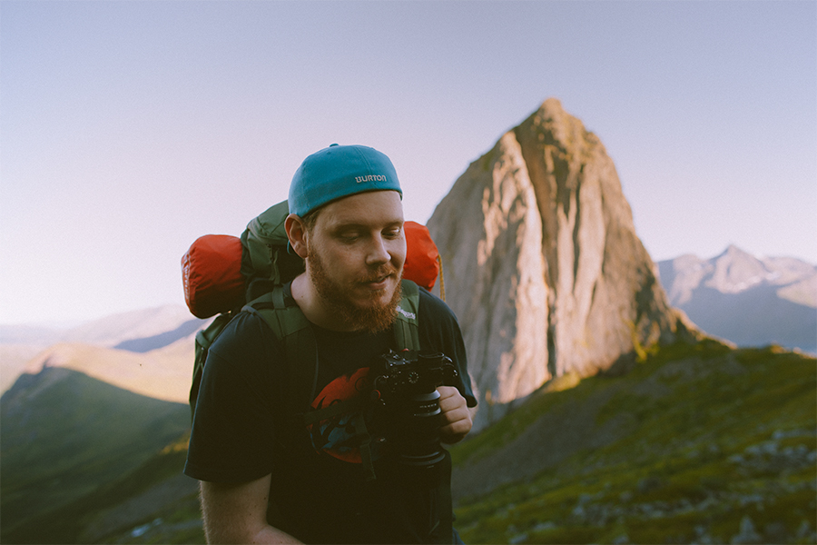 Man with blue caps and backpack together with Segla in Senja