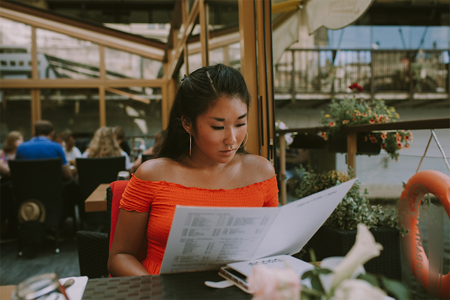 Girl wearing red looking at the menu