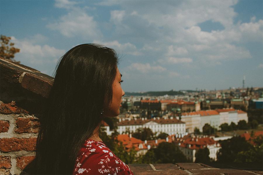 Girl wearing a red dress looking at Prague