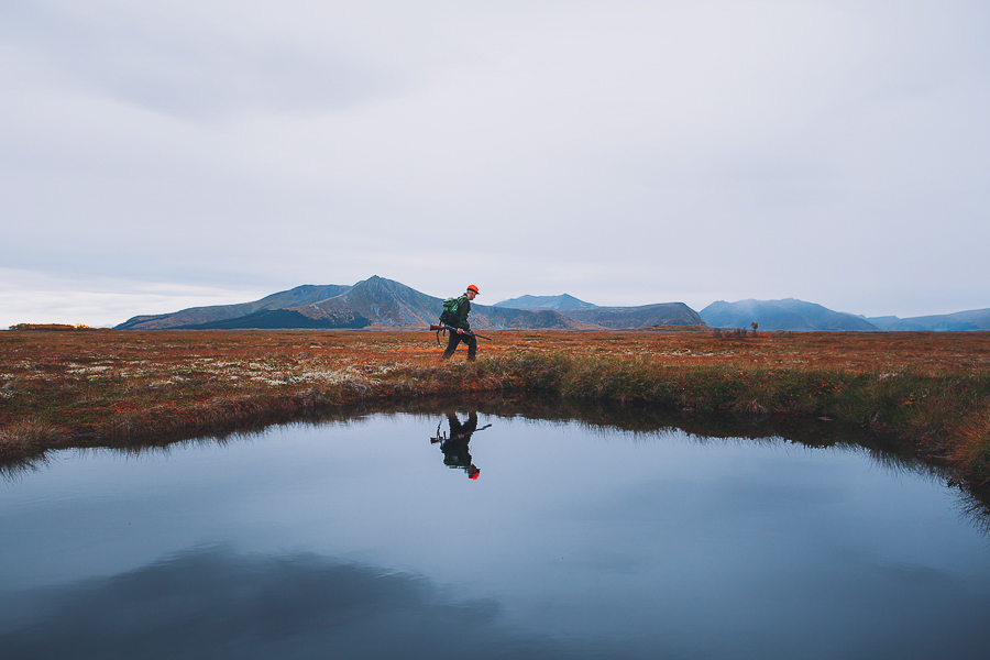Hunting man reflected in water