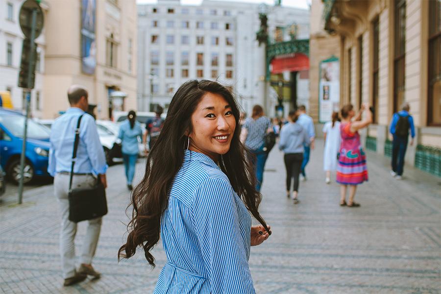 Girl in a blue shirt smiling in Prague