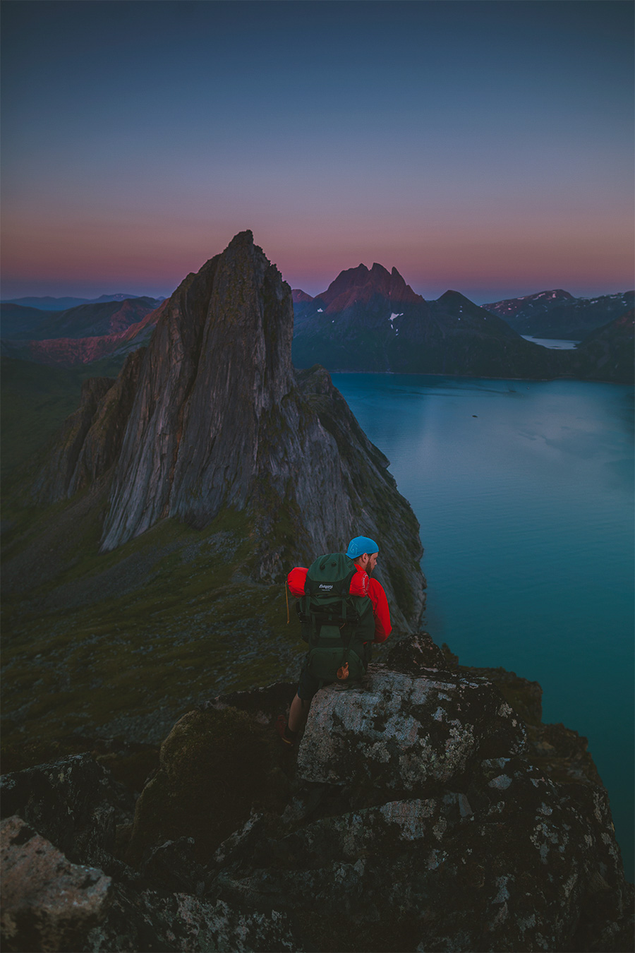 Man with a backpak looking at Segla in Senja
