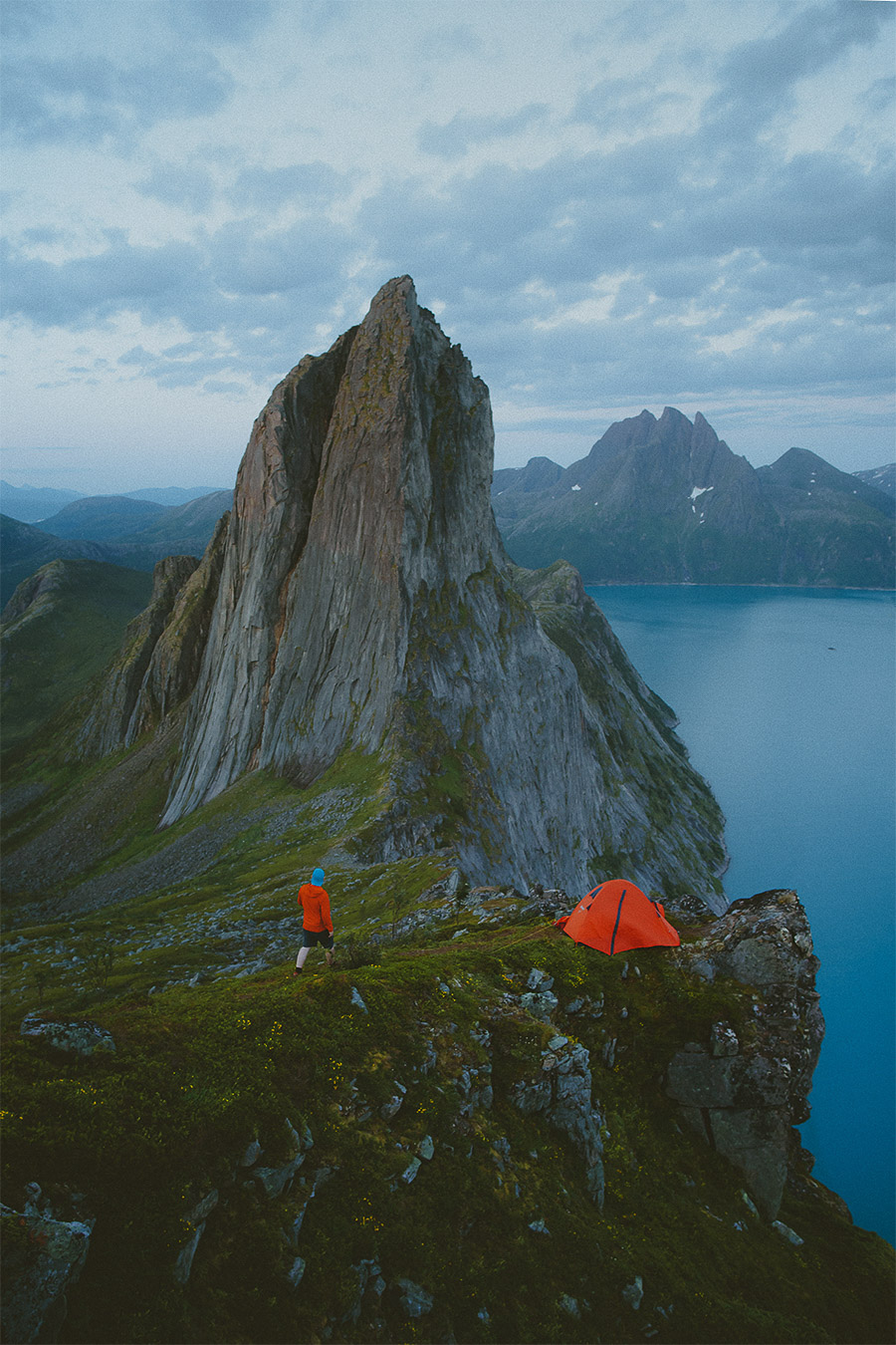 Orange tent and man in orange jacket in Senja
