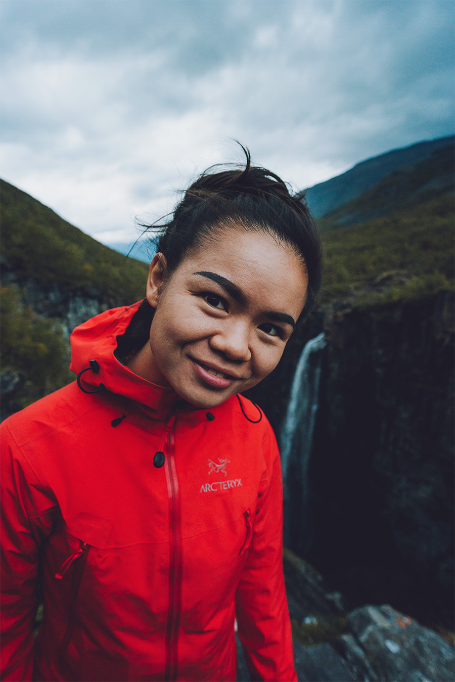 Girl in the orange jacket with a 120 meter waterfall in the background