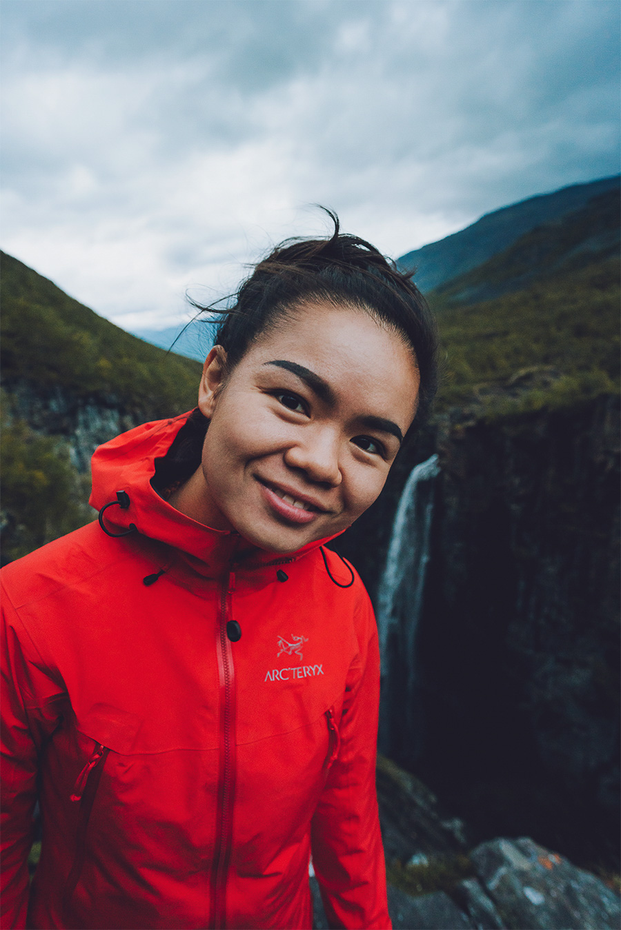 Smiling girl in an orange jacket with Gorsabrua located in Kåfjord in the background