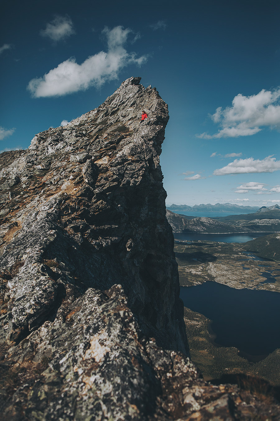 Girl in a red jacket on top of a cliff in Bodø