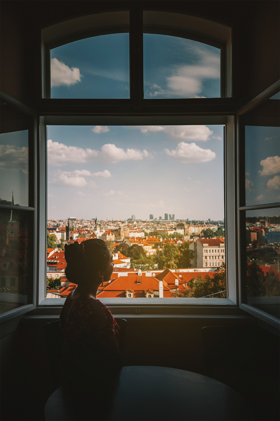 Girl by the window to Prague