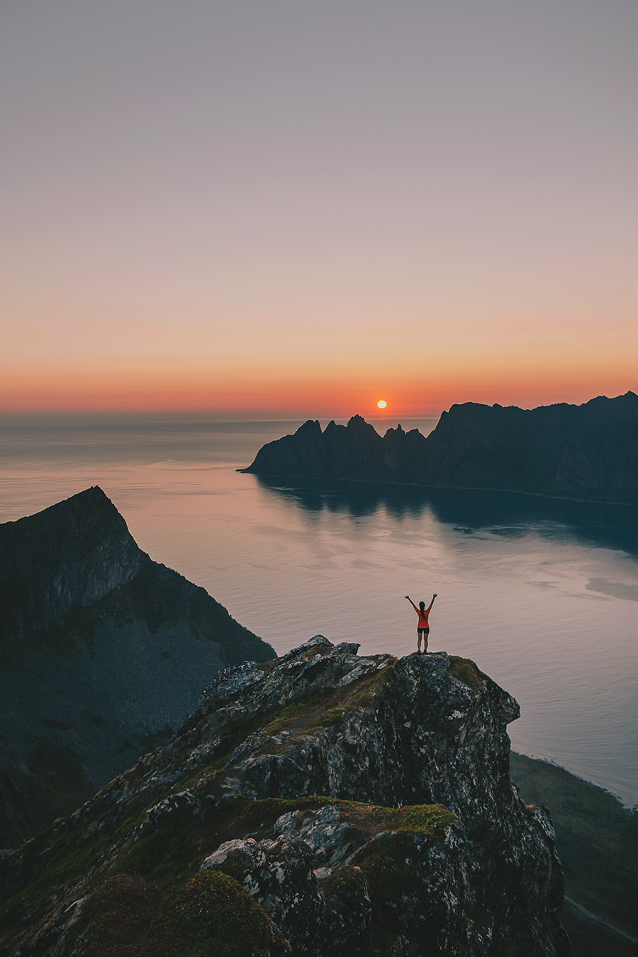 Girl raising her hands for the sunset