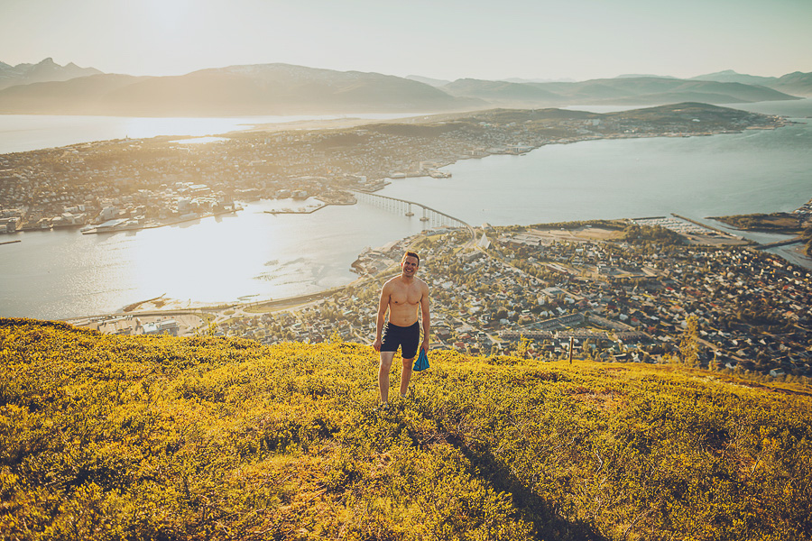 Boy hiking to Fjellheisen with Tromsø city as a sunny backdrop