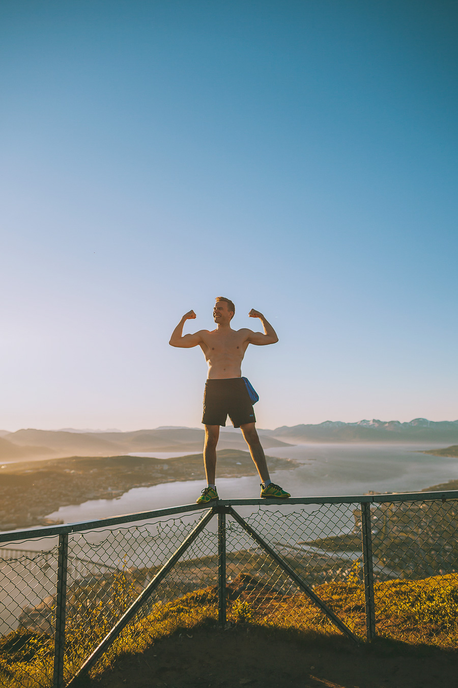Boy flexing on top of a fence at Fjellheisen