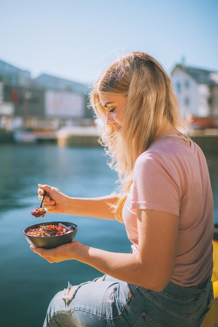 Girl eating a smoothie bowl at Tromsø harbour