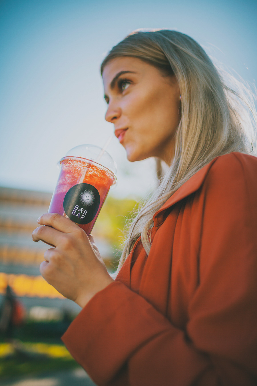 Blonde girl drinking strawberry smoothie