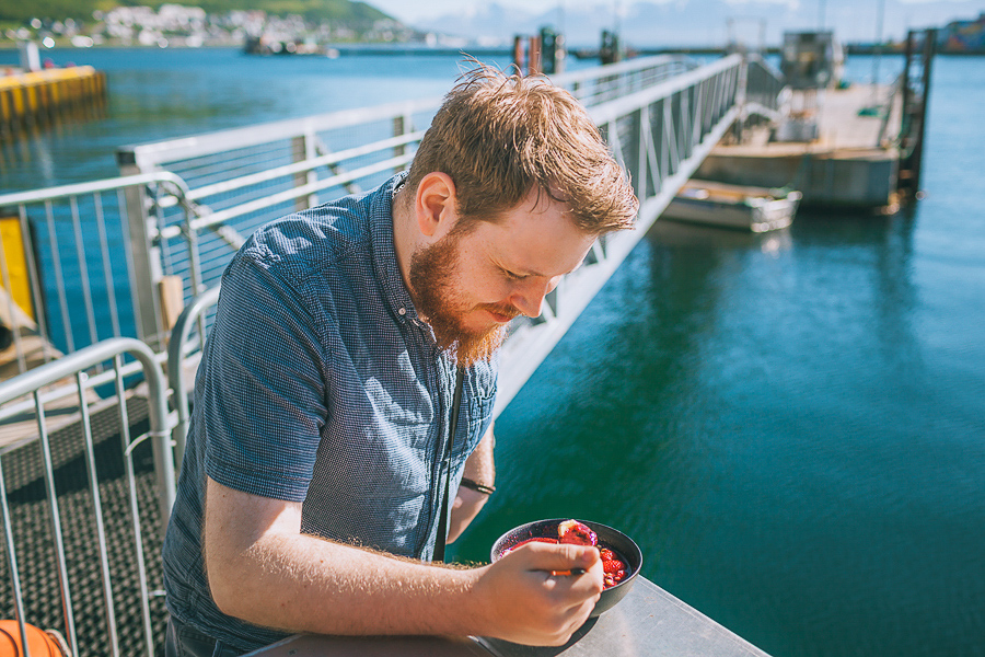 Man smiling while eating a smoothie bowl at Tromsø harbour
