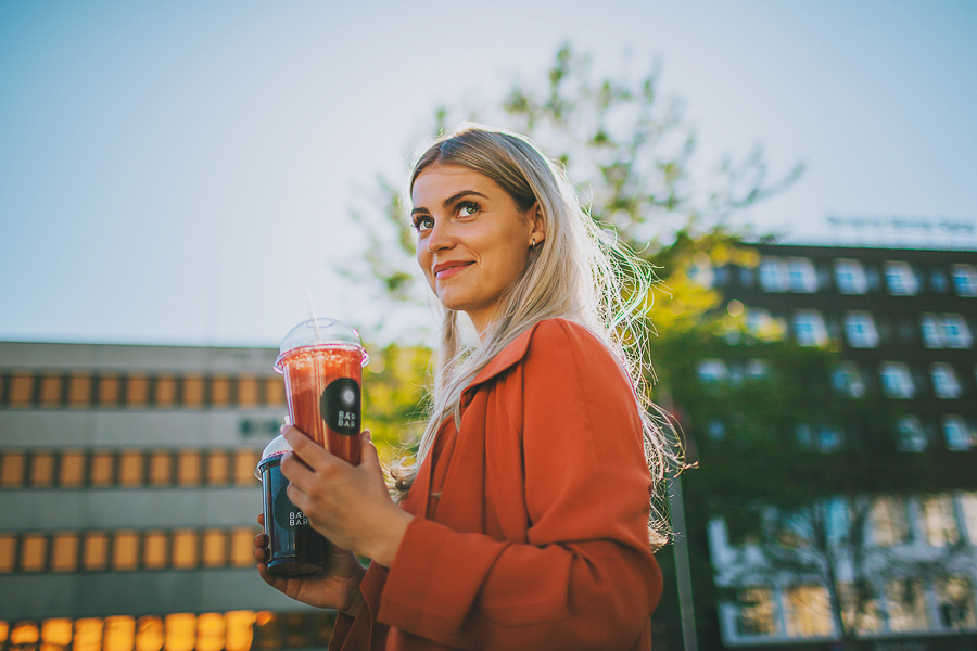 Blonde girl holding a red smoothie