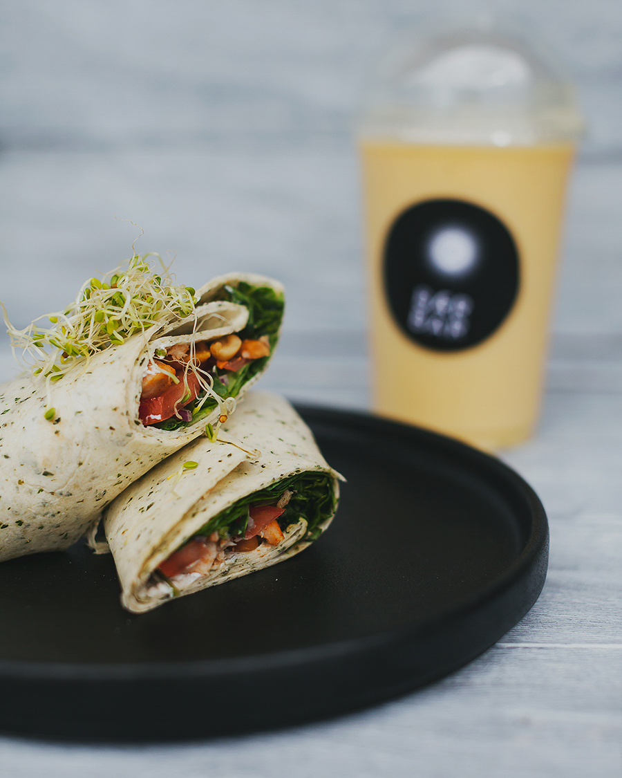 Wraps laying on a plate with a yellow smoothie in the background