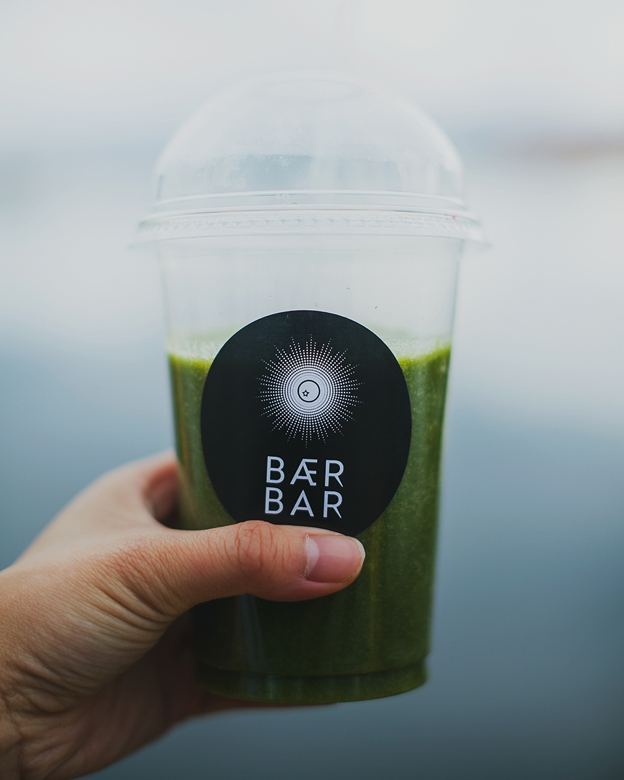 Hand holding a green smoothie