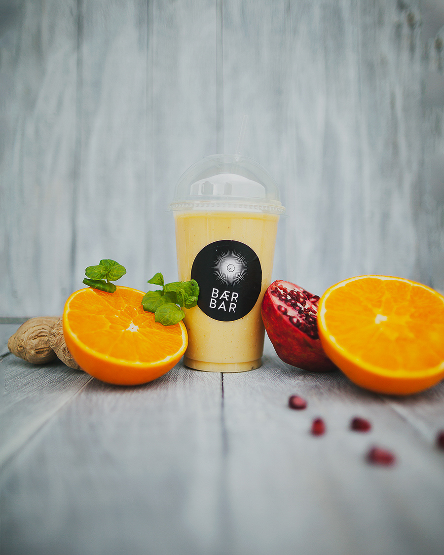 Yellow smoothie surrounded by fruits and berries