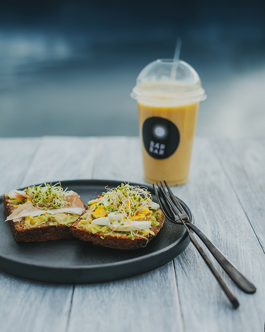 Sandwiches on a plate with a yellow smoothie in the background