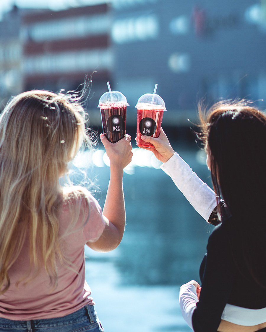 Two girls cheering with their smoothies