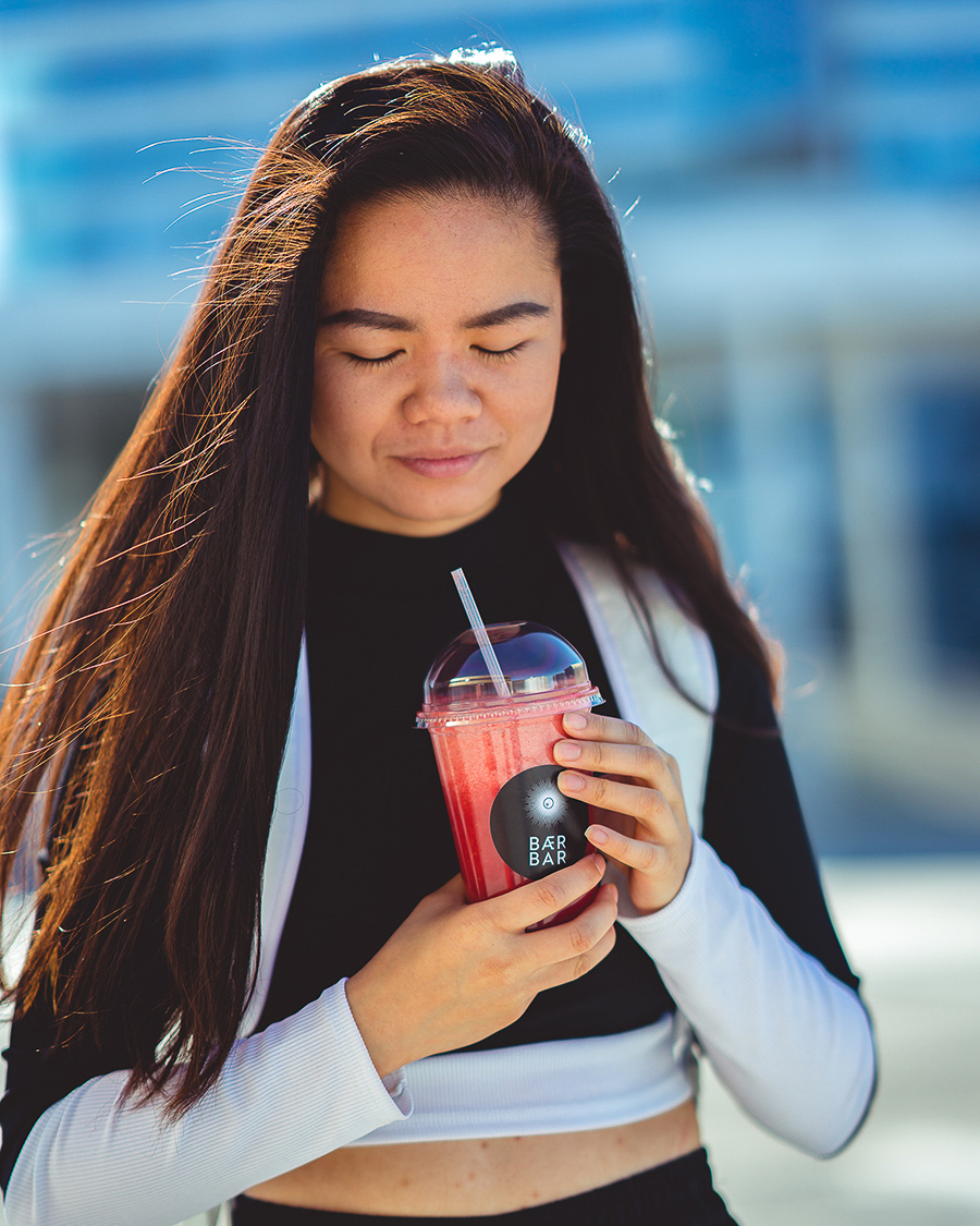 Girl with black hair holding a red smoothie
