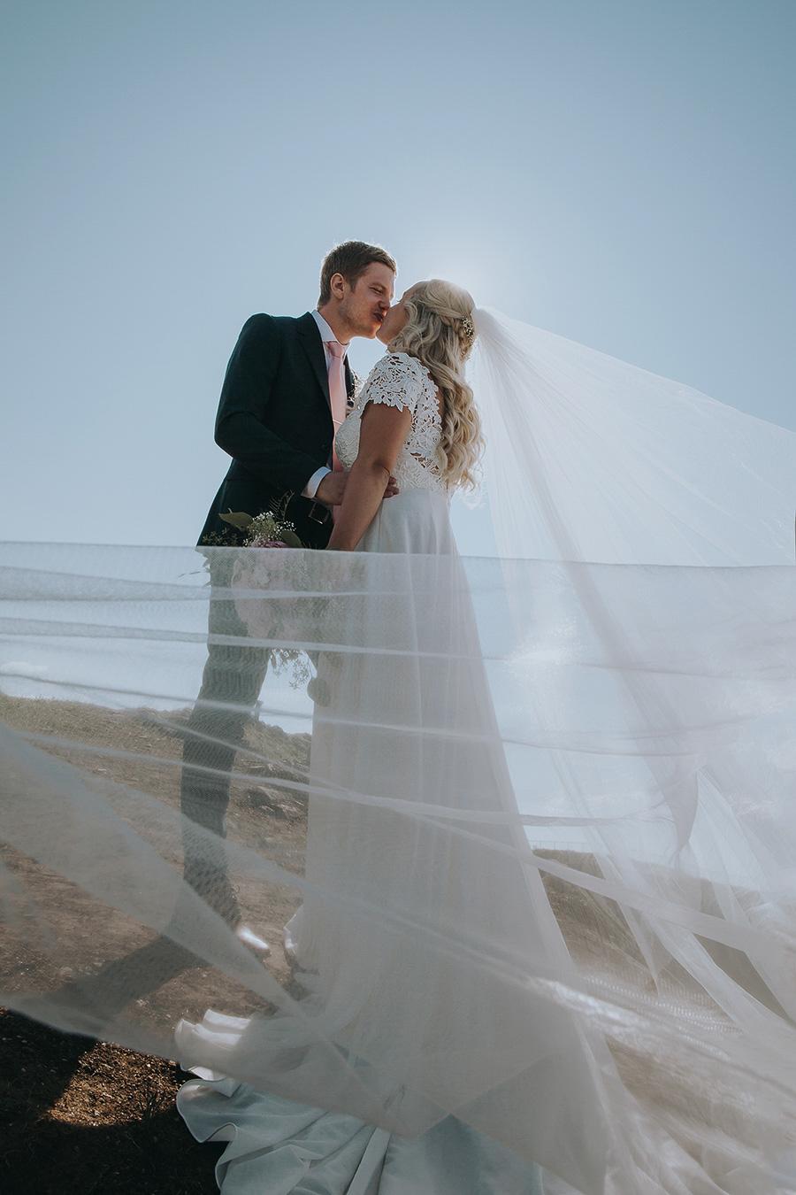 Bridal couple kissing in the sunlight in Tromsø
