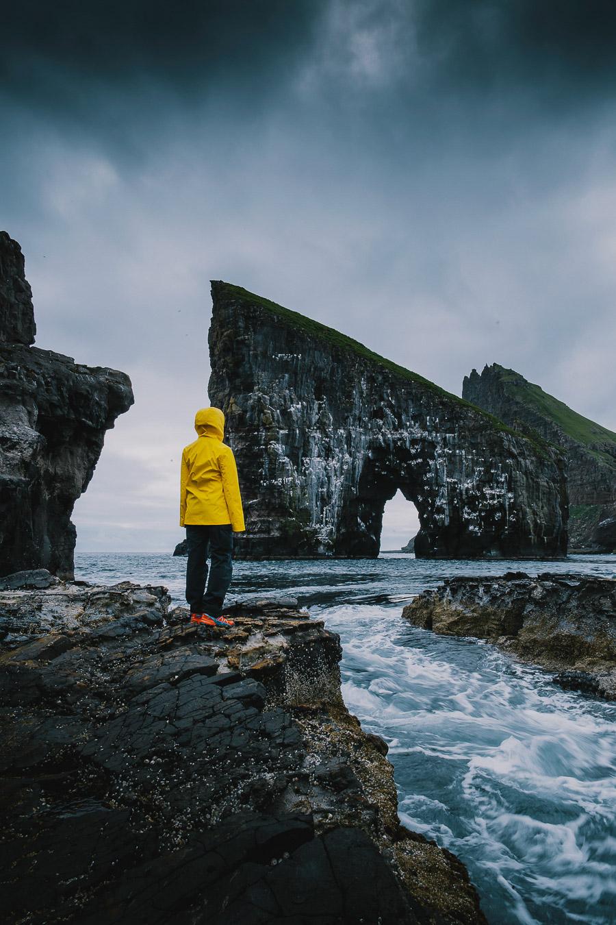 Woman in yellow jacket standing before Drangarnir in Faroe Islands