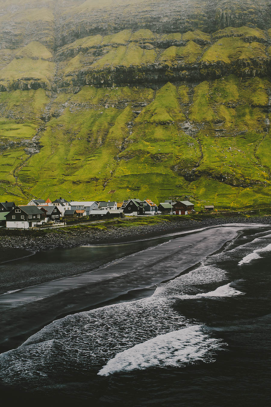Small village surrounded by green mountains and a black sandy beach