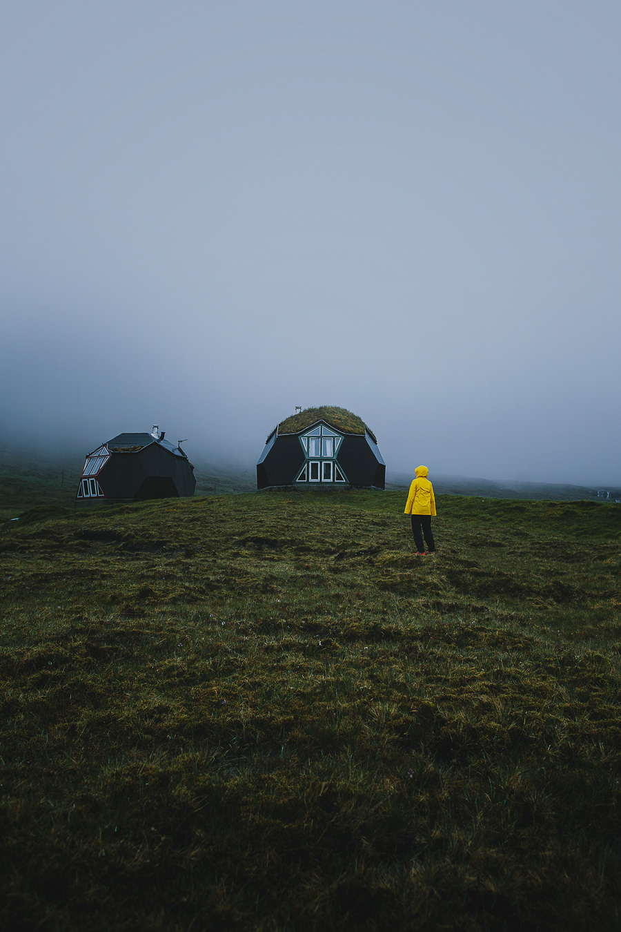 Woman in yellow jacket looking up at two round houses