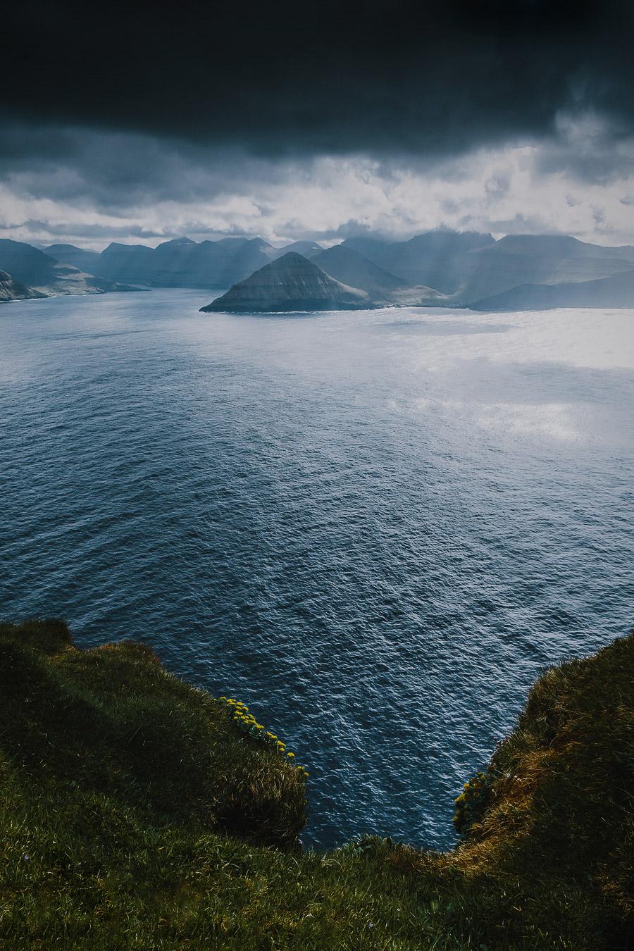 Blue ocean, tall mountains and sunlight in Faroe Islands