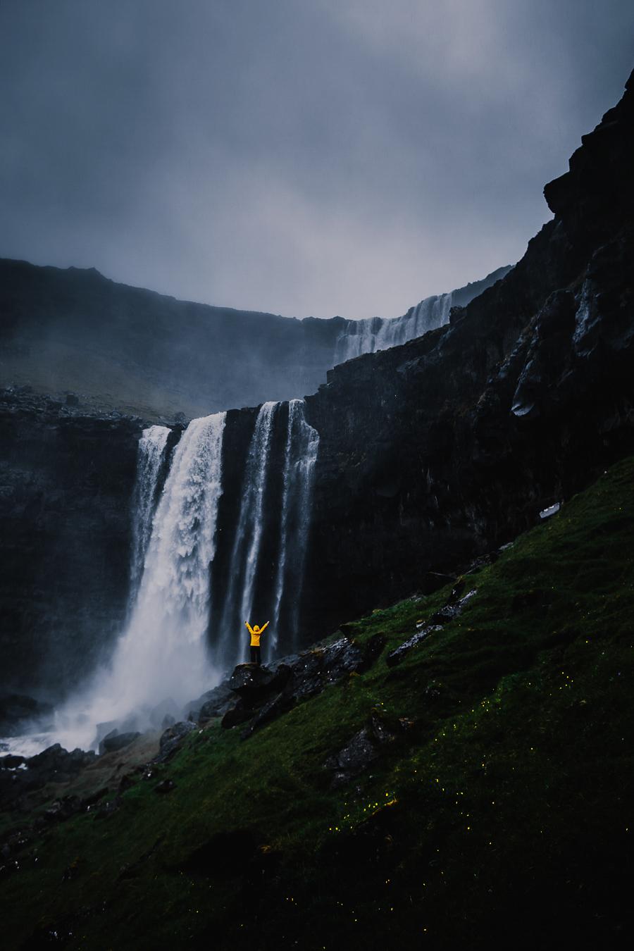 Person in yellow jacket before Fossa waterfall in Faroe Islands