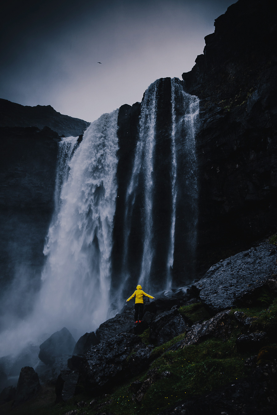 Yellow dressed person looking up at Fossa waterfall
