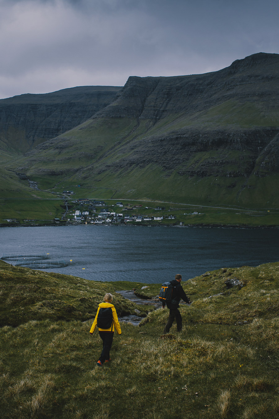 A woman and man hiking in the mountains of Faroe Islands