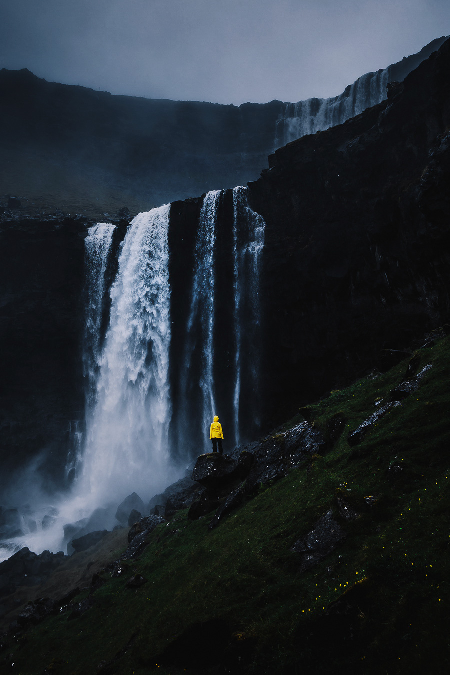 Yellow dressed woman standing in fron of a waterfall