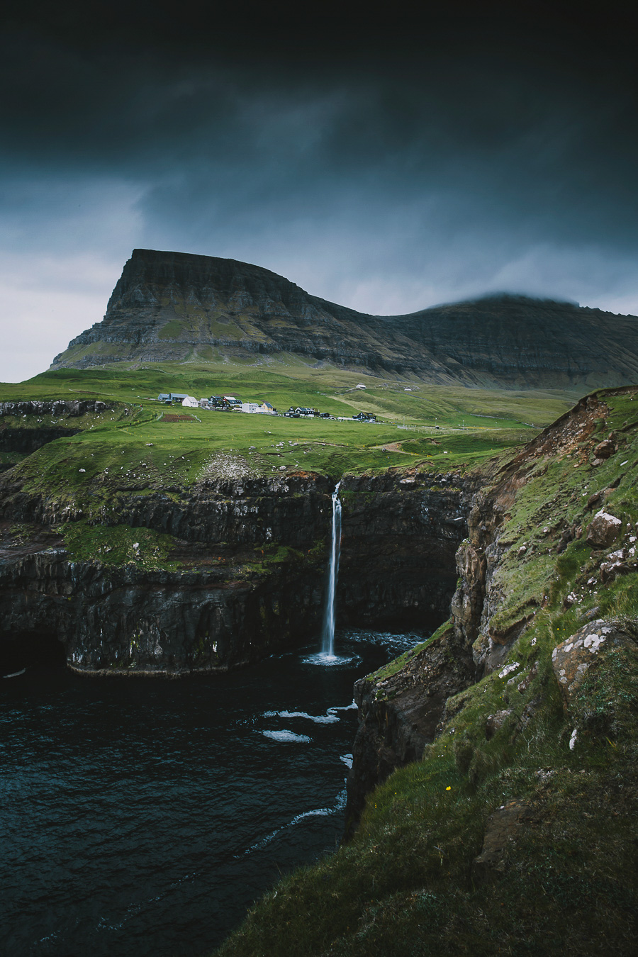 Houses by the waterfall and tall mountains
