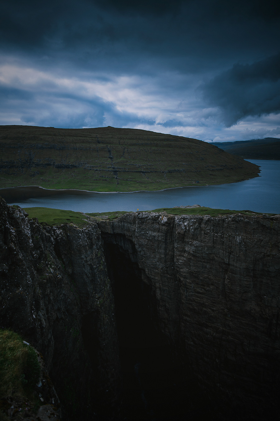 Yellow dressed woman standing by the floating lake in Faroe Islands