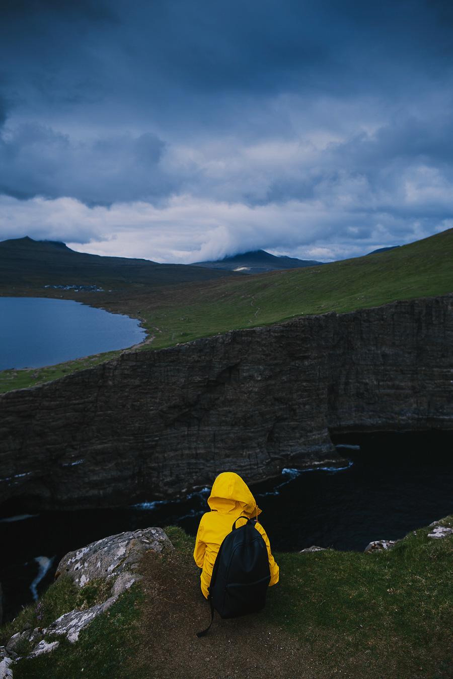 Woman in yellow jacket sitting on a cliff in Faroe Islands