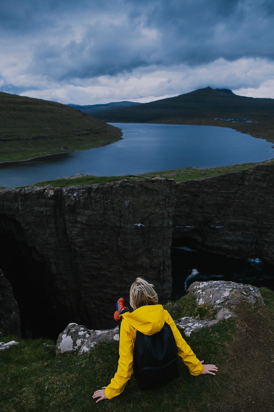 Yellow dressed woman sitting on the edge of Faroe Islands