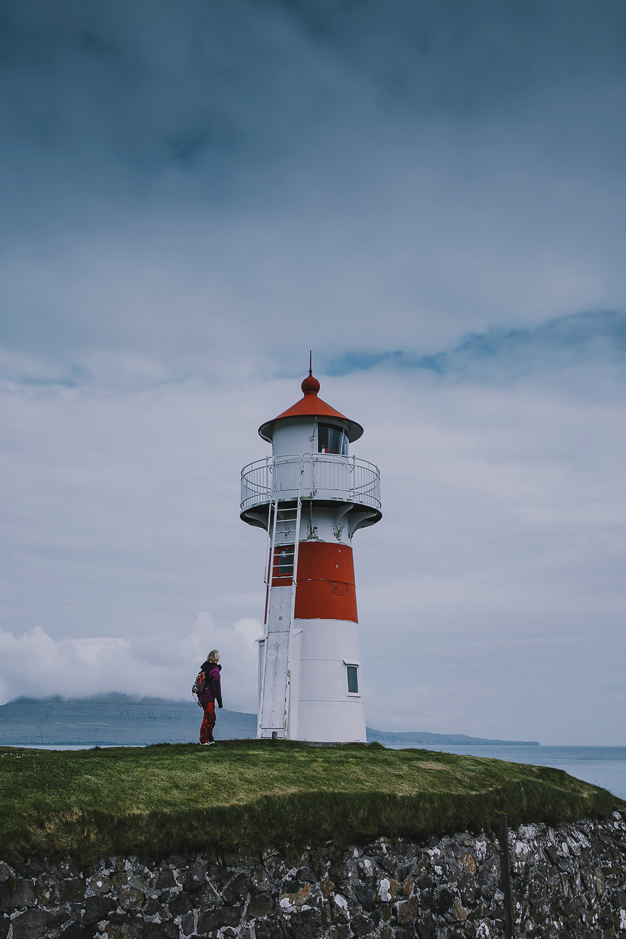 Person standing by the light house in Torshavn
