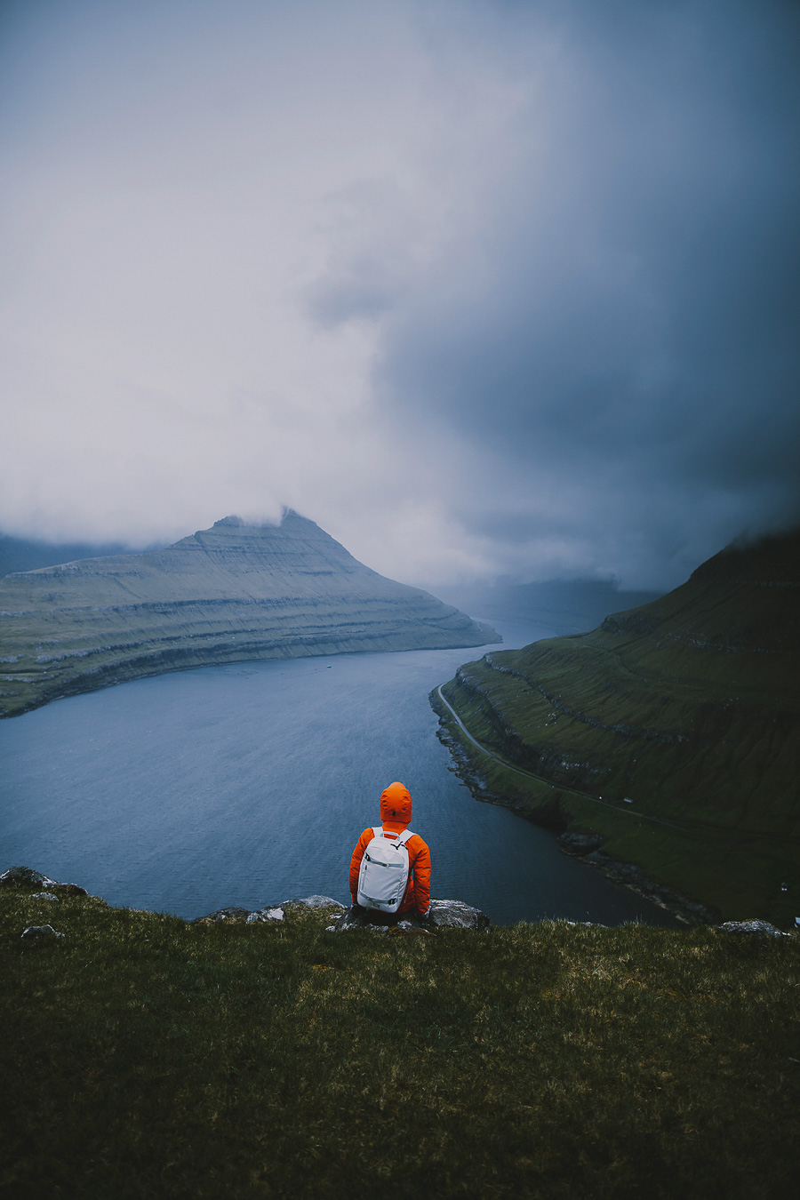 Girl in orange jacket with a white backpack sitting at the end of the world in Faroe Islands