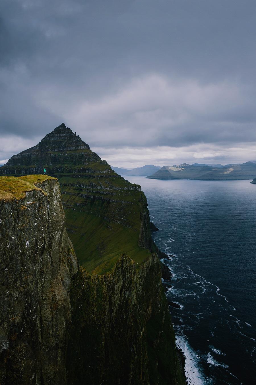 Man in green jacket standing on the cliff in Faroe Islands