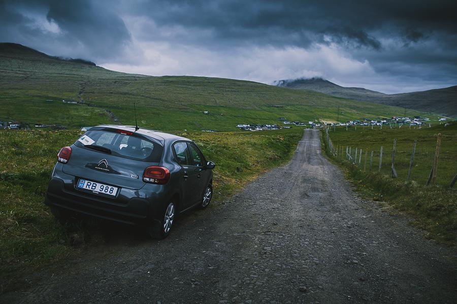 Blue rental car on a road in Faroe islands