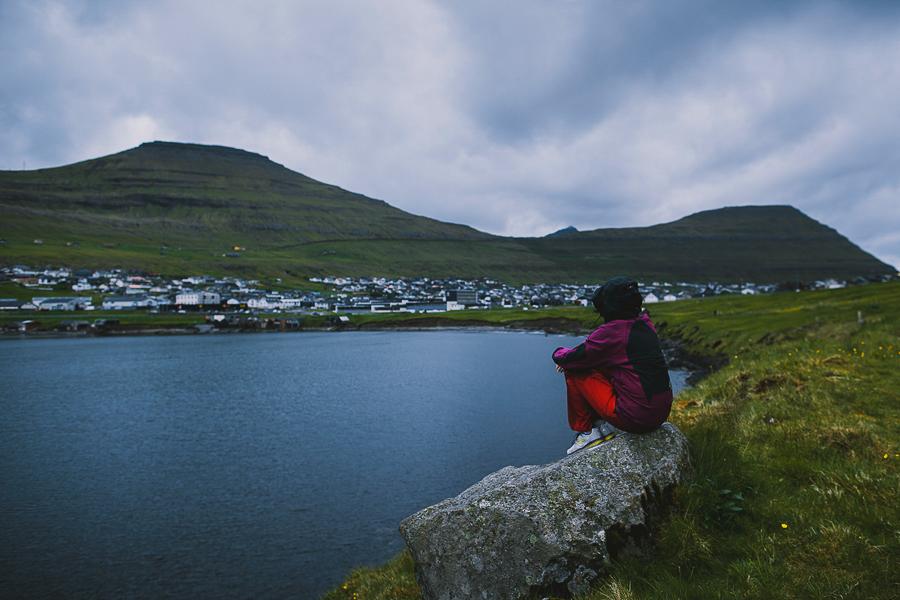 Person sitting by the ocean in Faroe Islands