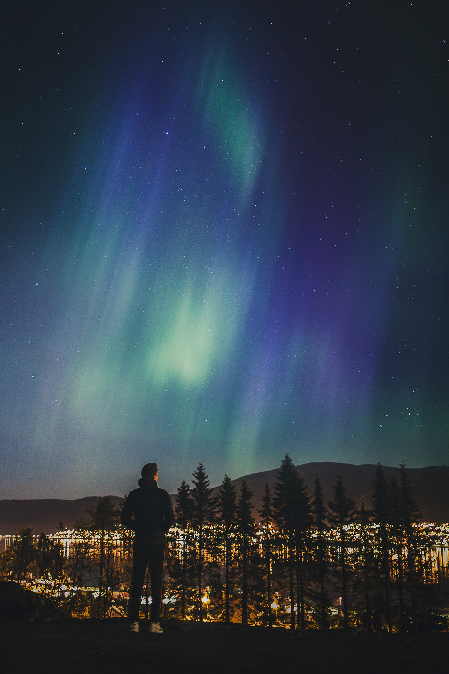 Boy staring at the northern lights dancing on the sky