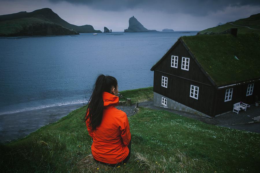 Girl in orange jacket exploring Bøur in Faroe Islands