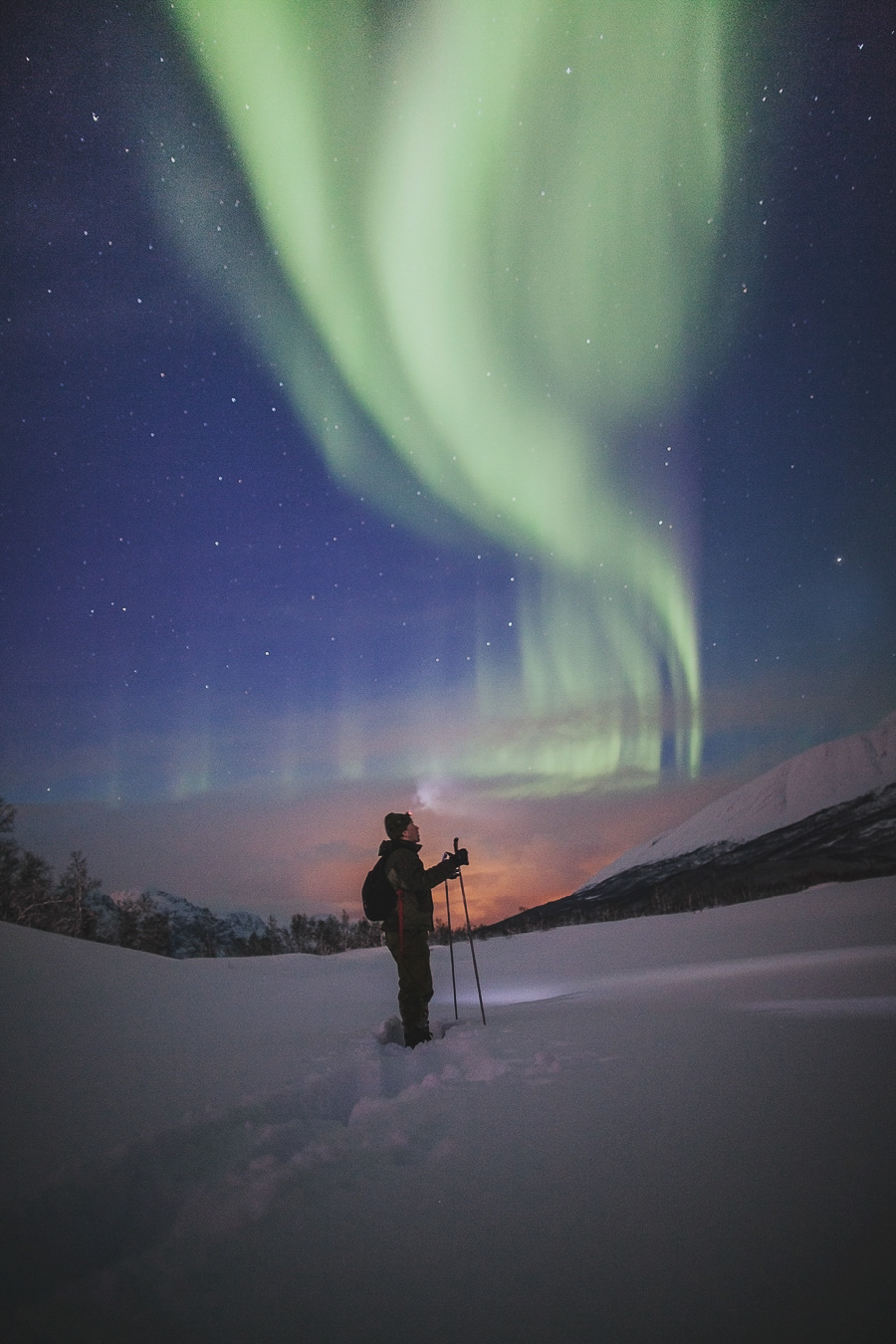 Man looking up at the northern lights in Tromsø