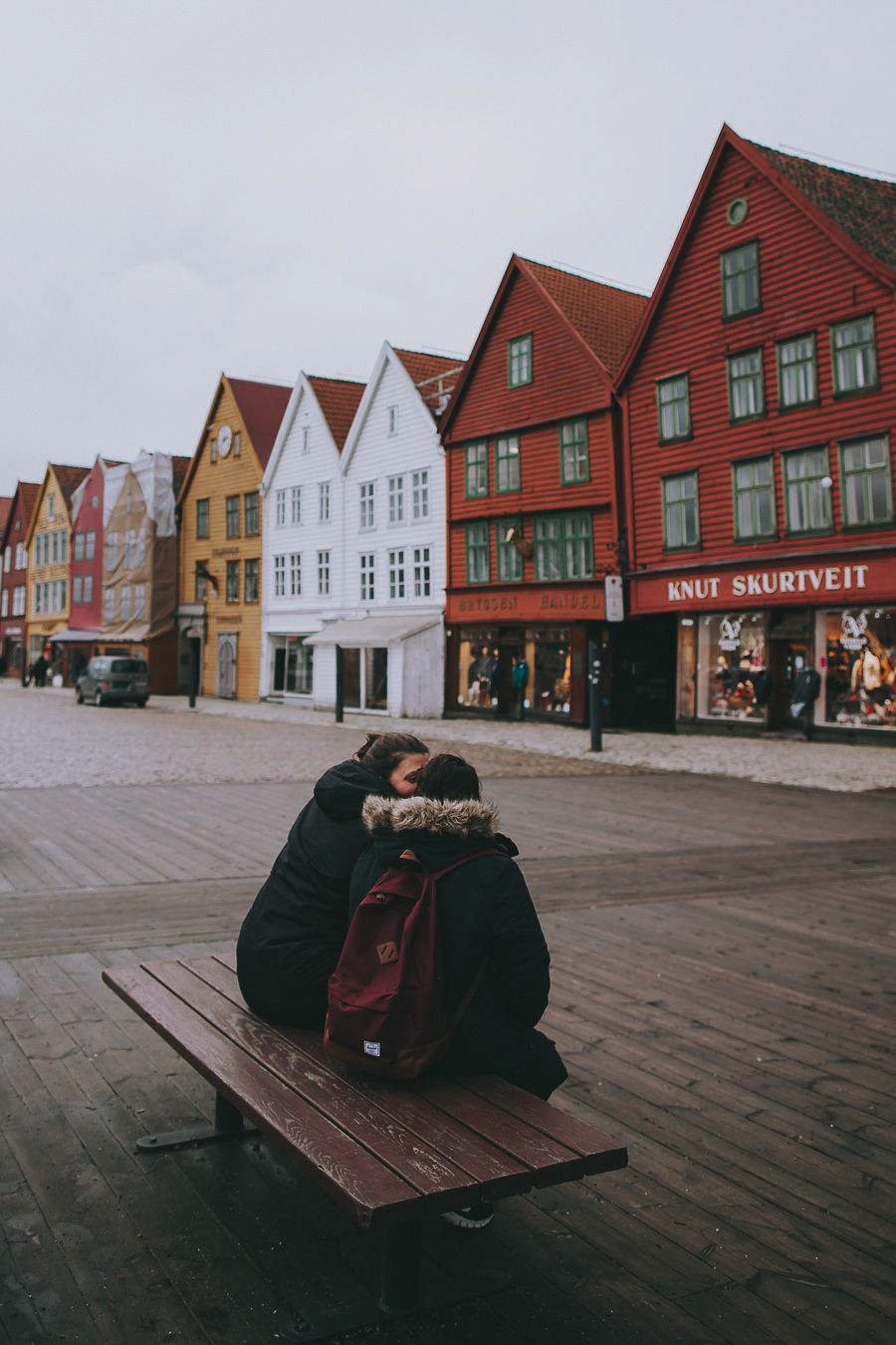 Couple sitting on a bench at Bryggen in Bergen